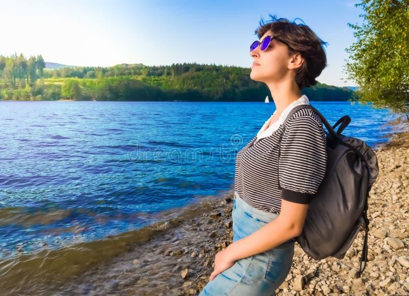 Uma mulher no banco do rio põe sua cara ao sol imagens de stock