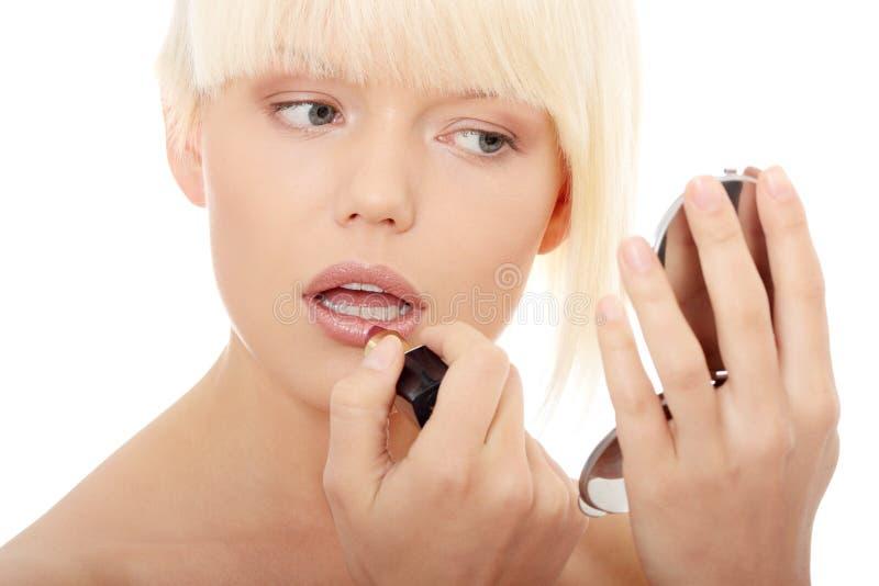 Uma mulher nova bonita que aplica sua composição foto de stock