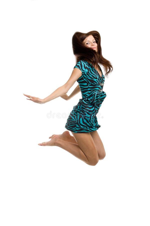 Uma mulher nova bonita que salta altamente no ar fotografia de stock royalty free