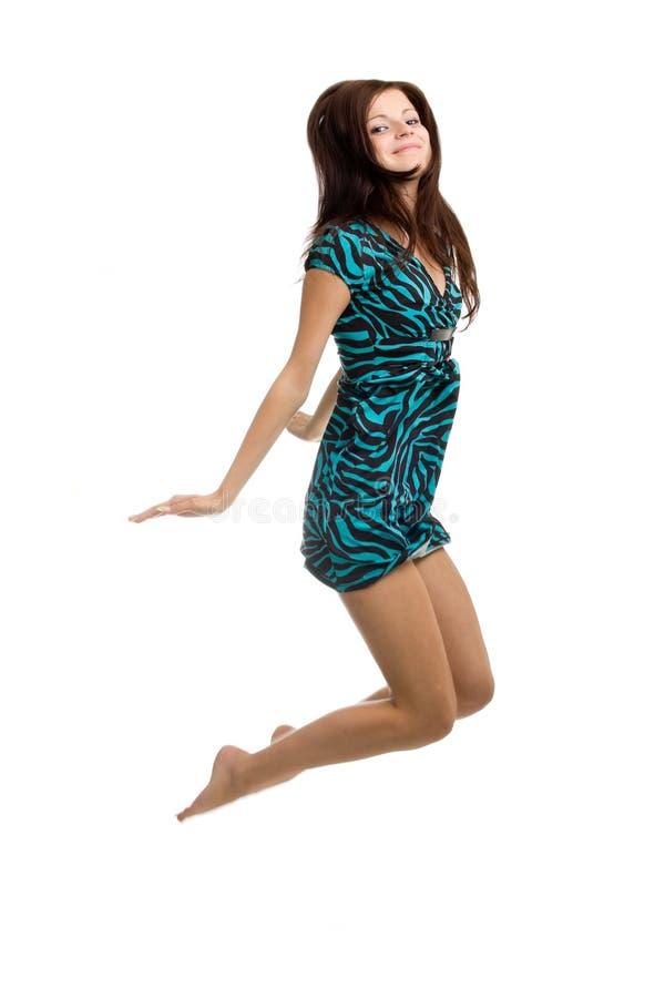 Uma mulher nova bonita que salta altamente no ar fotos de stock royalty free