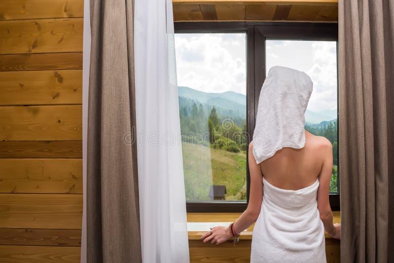 Uma mulher nova, bonita, 'sexy', depois que um chuveiro, suportes envolvidos em uma toalha perto da janela no hotel com uma vista imagens de stock