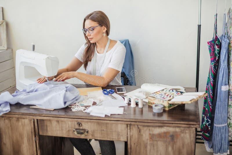 Uma mulher nova da costureira costura a roupa em uma máquina de costura Costureira de sorriso em sua oficina imagens de stock