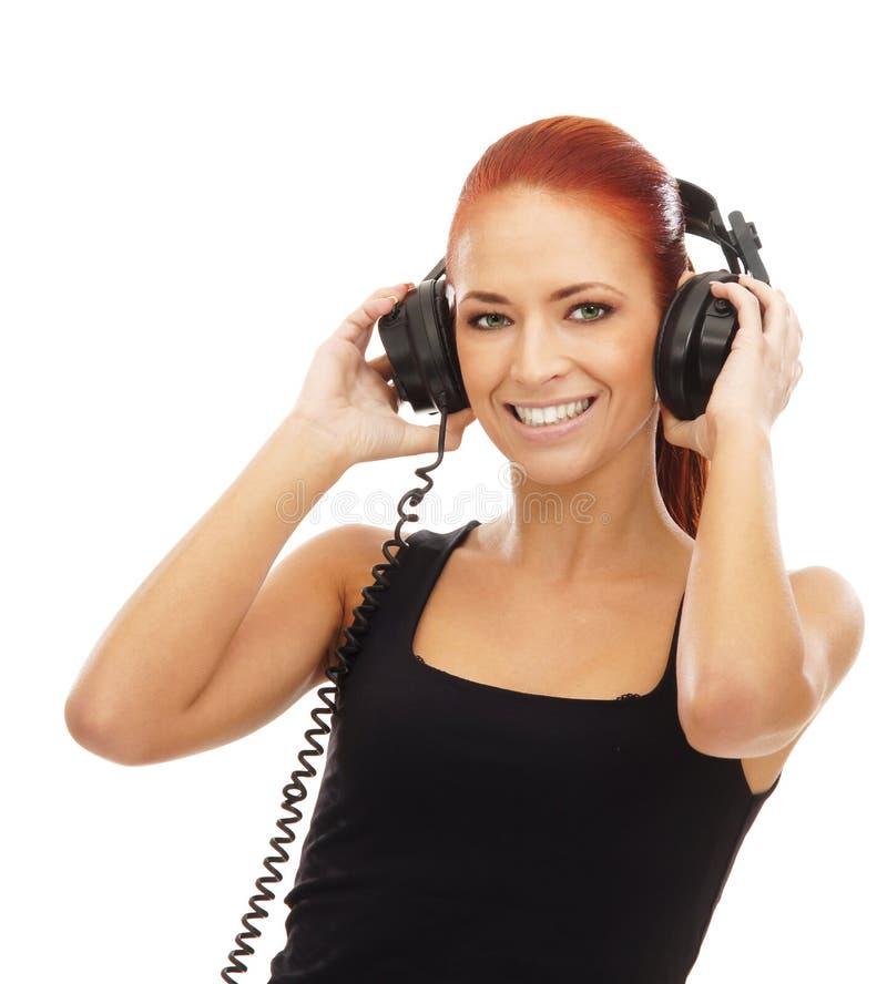 Uma mulher nova do redhead que escuta a música foto de stock royalty free