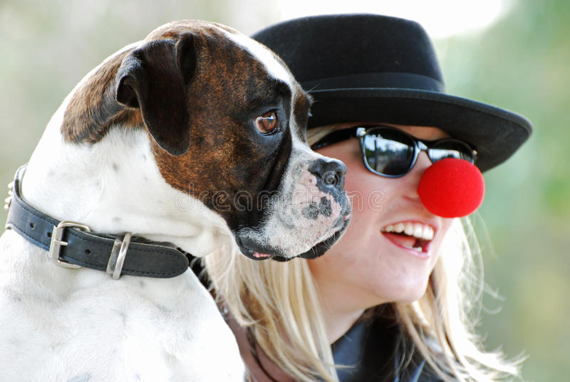 Uma mulher nova encantadora que ri com seu cão do pugilista fotografia de stock royalty free