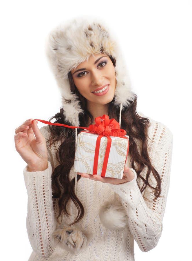 Uma mulher nova no inverno veste a abertura de um presente fotografia de stock
