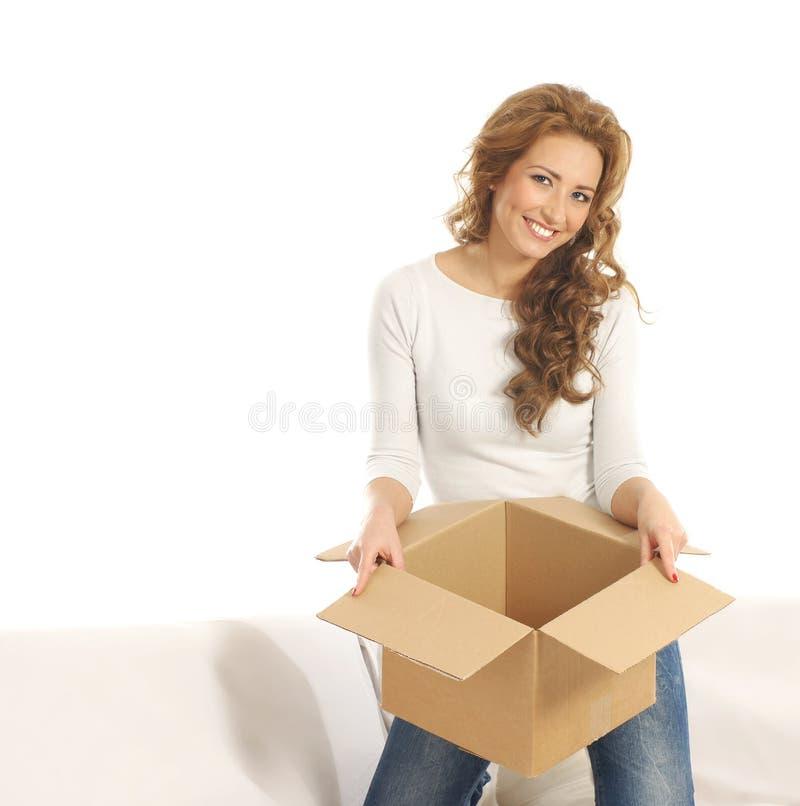 Uma mulher nova que prende uma caixa de cartão aberta fotografia de stock royalty free