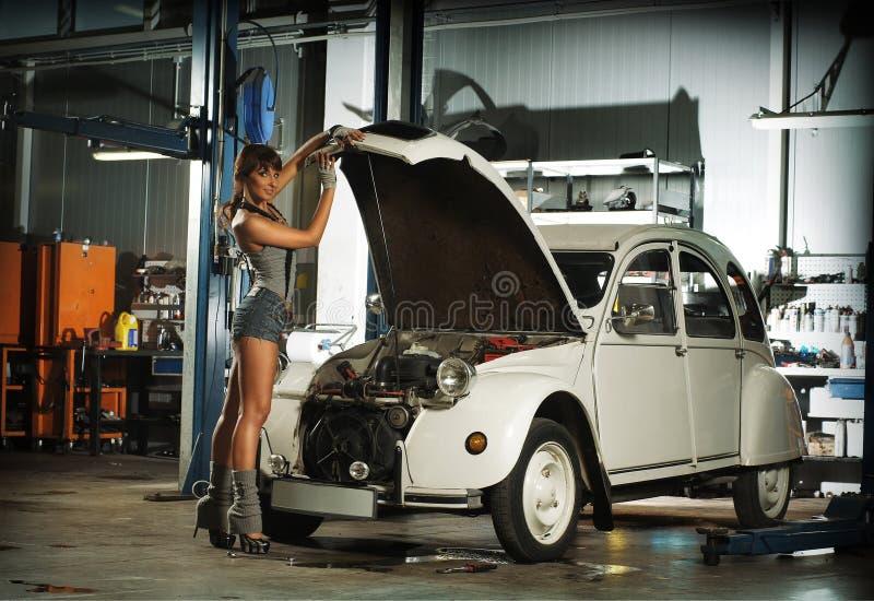Uma mulher nova que repara um carro retro em uma garagem imagens de stock royalty free