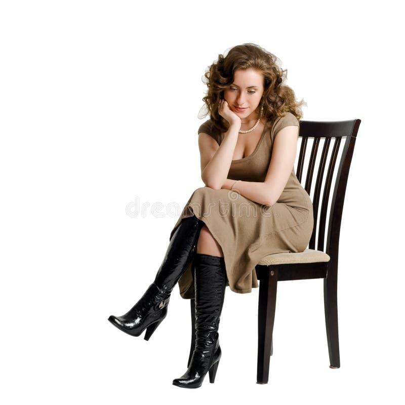 Uma mulher nova triste que senta-se em uma cadeira fotografia de stock royalty free