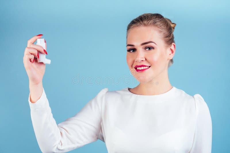 Uma mulher numa blusa branca segura um inalador sobre um fundo azul foto de stock