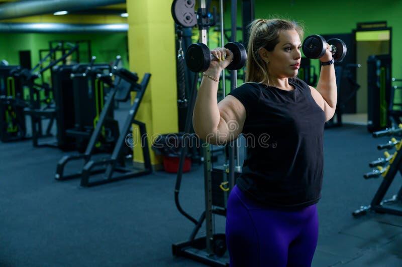 Uma mulher obesa está trabalhando para perder peso Biceps de comboio loiros gordos com uma campainha na sala de estagiários Muita foto de stock
