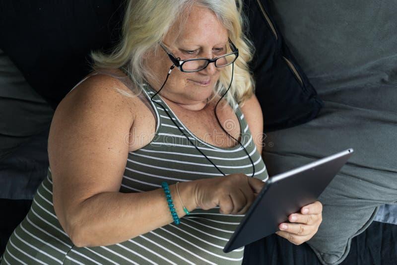 Uma mulher obeso mais idosa que coloca na cama olha uma tabuleta imagens de stock royalty free