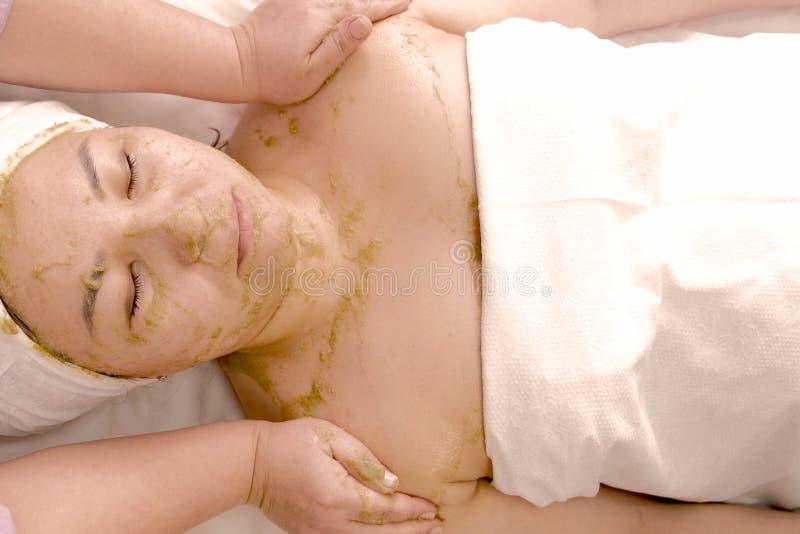 Uma mulher obtém uma máscara da saúde das algas verdes Retrato da vista superior da menina asiática em uma toalha que encontra-se imagens de stock royalty free