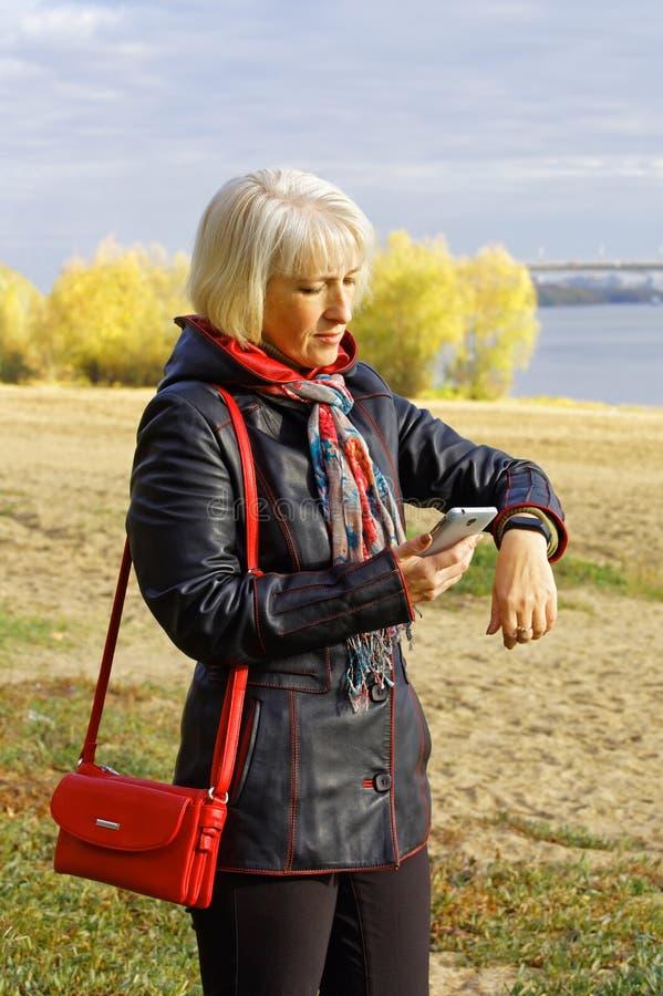 Uma mulher olha os resultados de sua atividade para este dia fotos de stock royalty free