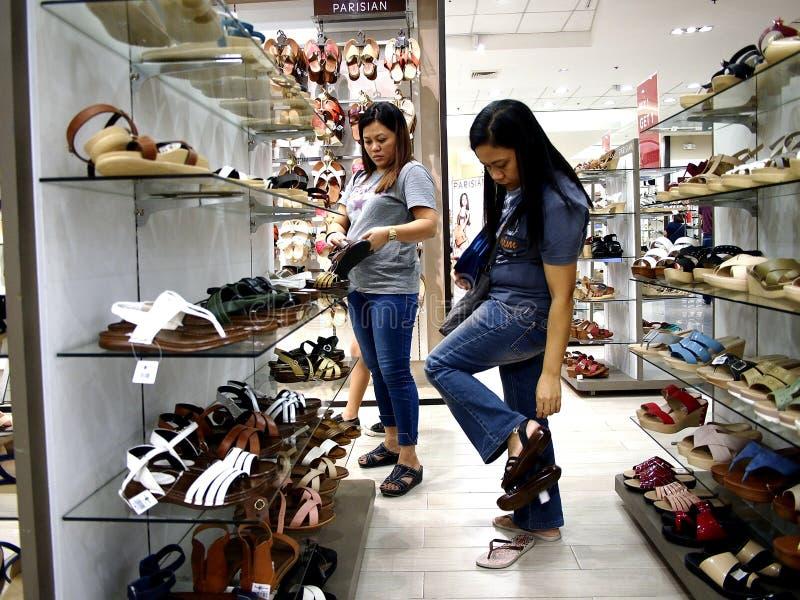 Uma mulher olha um par de sapatas no departamento da sapata da alameda da cidade da manutenção programada na cidade de Taytay, Fi fotos de stock