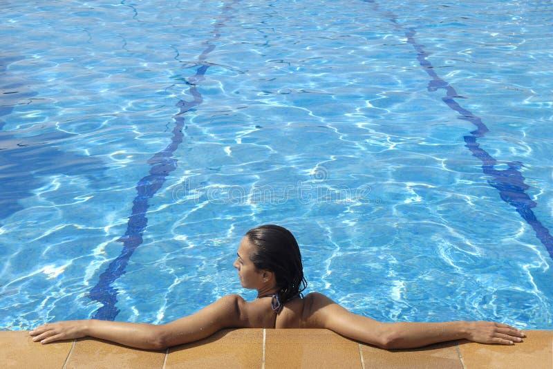 Uma mulher pela piscina brilhante foto de stock royalty free