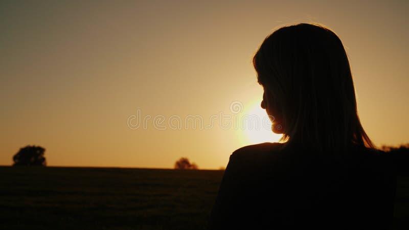 Uma mulher pensativa olha o sol de ajuste, a vista traseira Os sonhos e o conceito da solidão, olham para a frente foto de stock