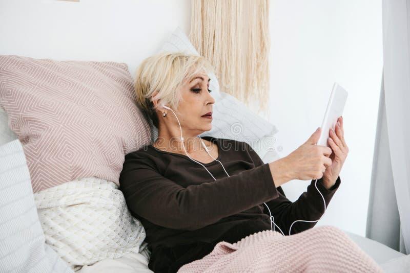 Uma mulher positiva mais idosa usa uma tabuleta para olhar vídeos, escutar a música e para conversar com os amigos em redes socia imagem de stock royalty free