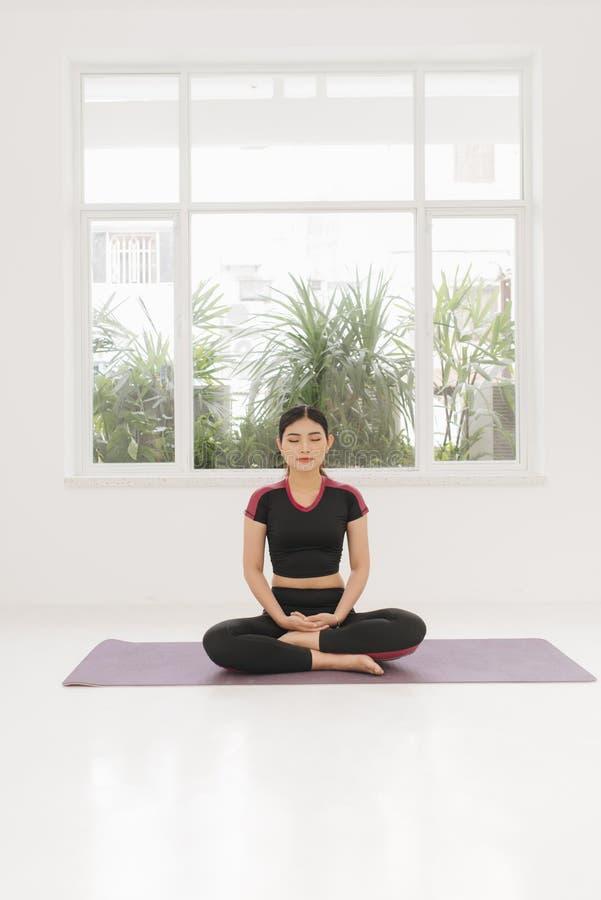 Uma mulher pratica a ioga perto da janela fotos de stock royalty free