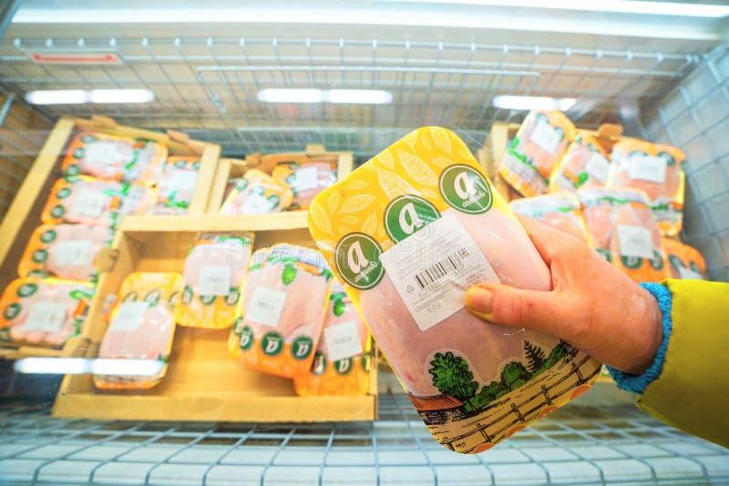 Uma mulher puxa a carne empacotada da galinha de um congelador em imagens de stock