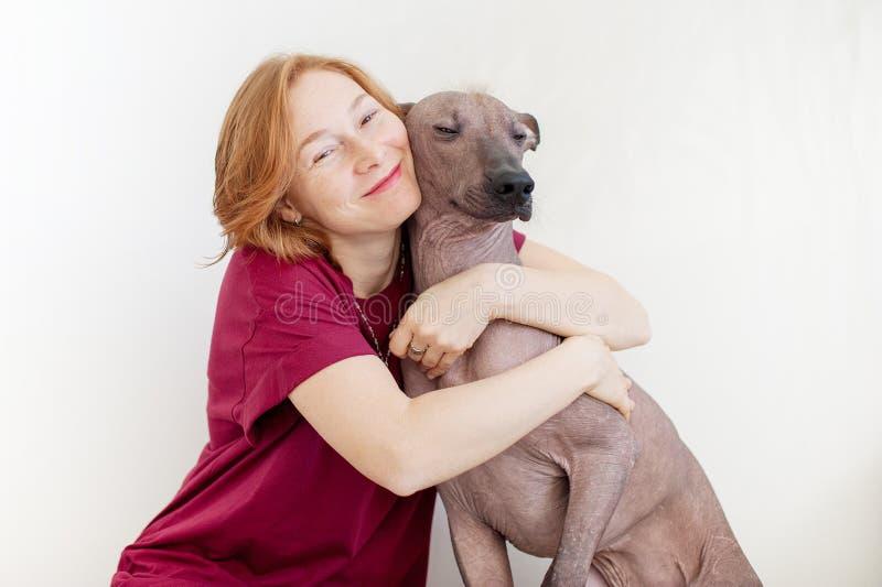 Uma mulher que abraça com um cão imagens de stock