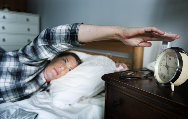 Uma mulher que acorda a um alarme foto de stock royalty free