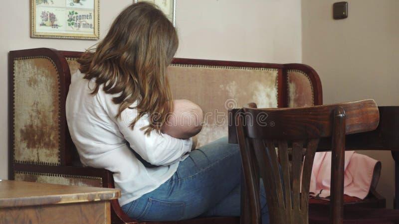 Uma mulher que amamenta sua criança em um café imagens de stock