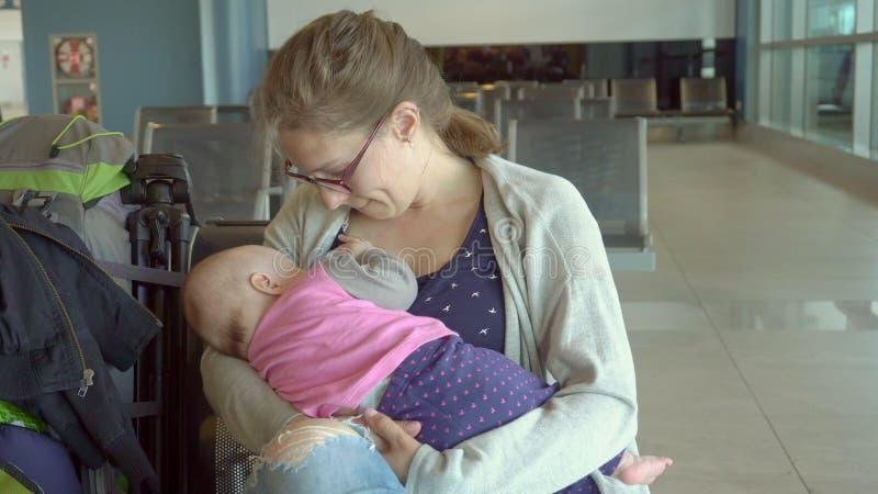 Uma mulher que amamenta sua criança no aeroporto imagens de stock