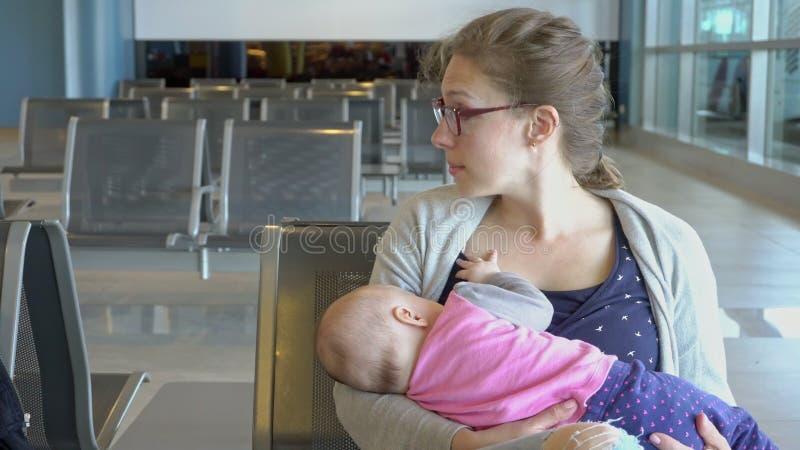 Uma mulher que amamenta sua criança no aeroporto imagem de stock