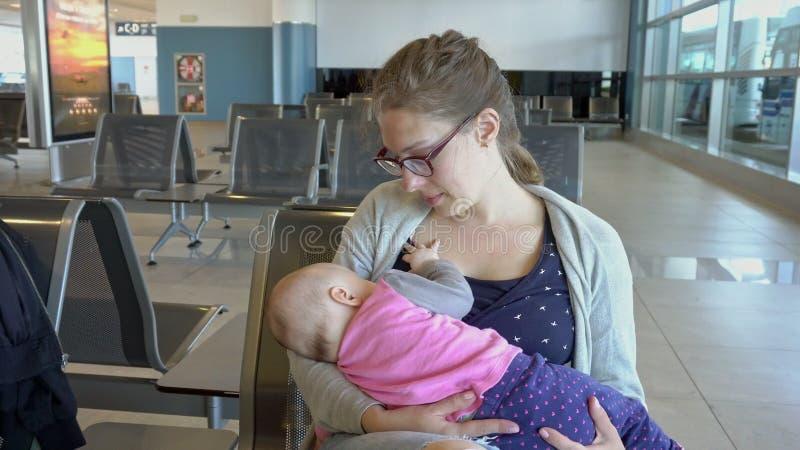 Uma mulher que amamenta sua criança no aeroporto fotos de stock royalty free