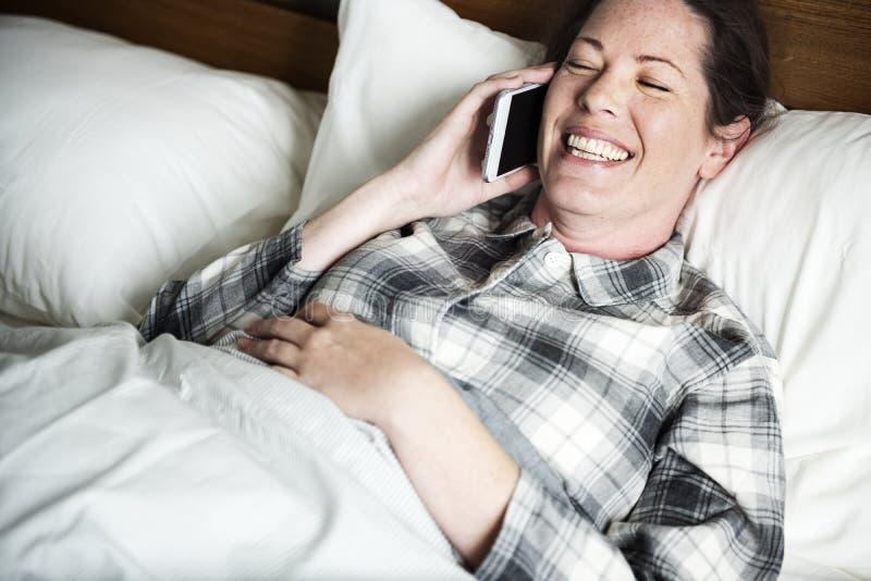 Uma mulher que chama alguém na cama foto de stock royalty free