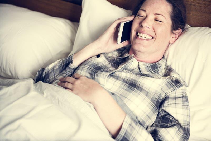 Uma mulher que chama alguém na cama fotografia de stock royalty free