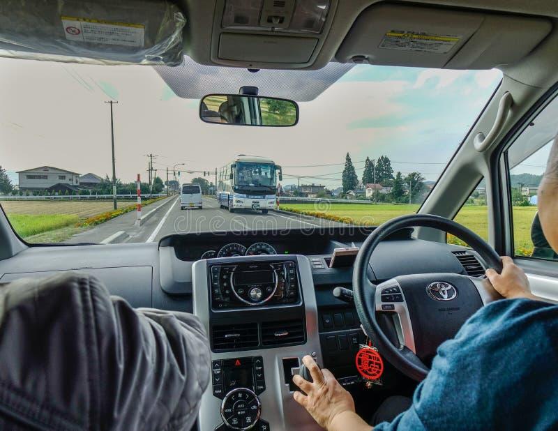 Uma mulher que conduz o carro na estrada rural fotografia de stock