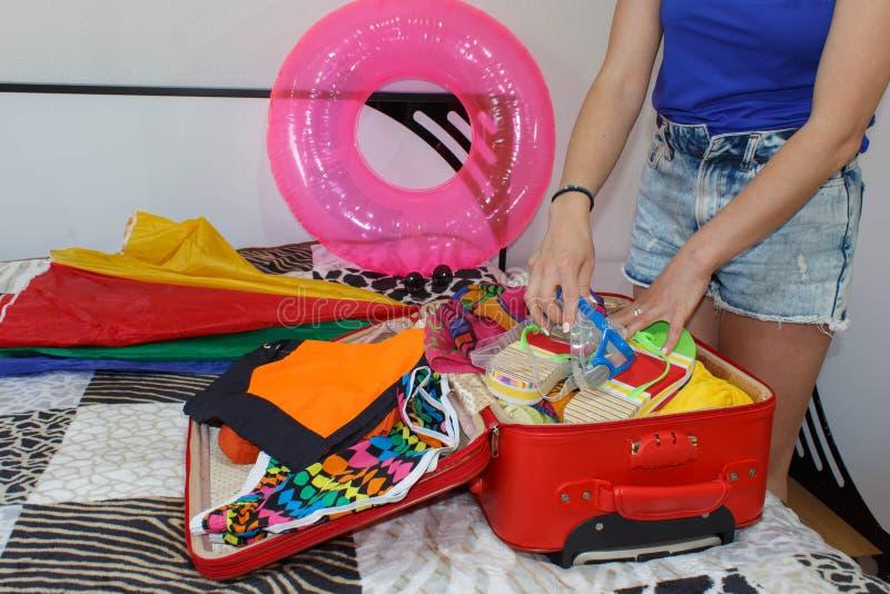 Uma mulher que embala uma bagagem para uma viagem nova imagem de stock royalty free