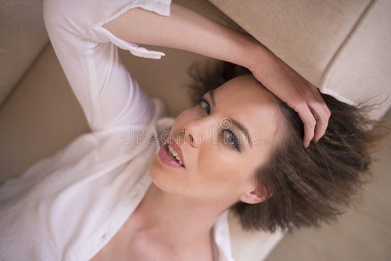Uma mulher que encontra-se para baixo em seu sofá que relaxa imagem de stock royalty free