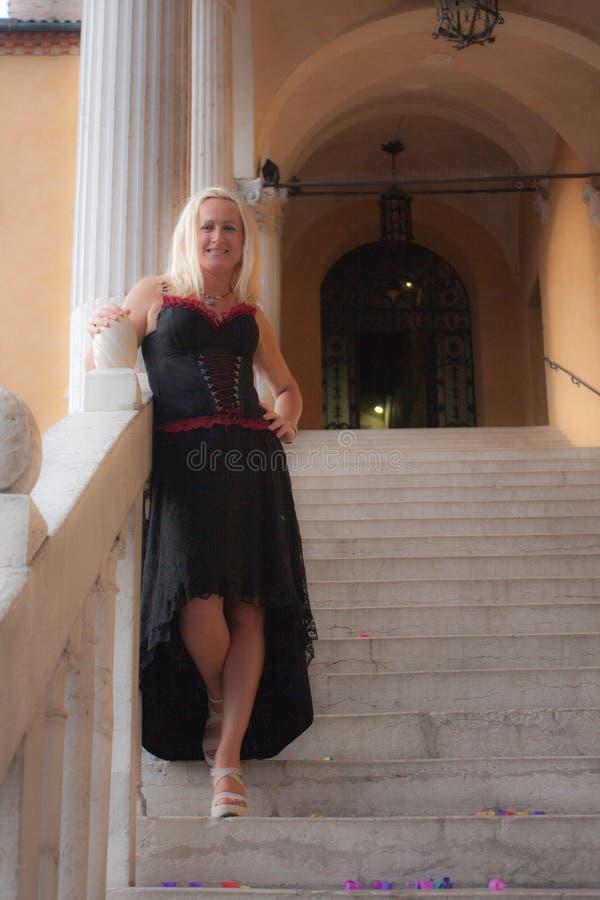 Uma mulher que espera nas escadas foto de stock