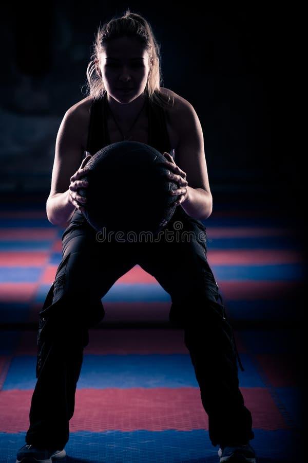 Uma mulher que faz uma ocupa com sua bola de medicina fotografia de stock royalty free