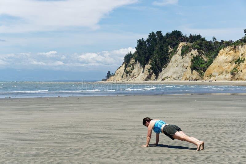 Uma mulher que fazer empurra levanta em Kina Beach em um dia ensolarado em Nova Zelândia fotografia de stock