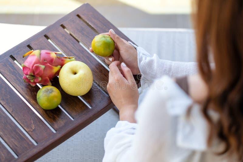 Uma mulher que guarda uma laranja com pera e fruto do dragão em uma tabela de madeira pequena imagens de stock royalty free