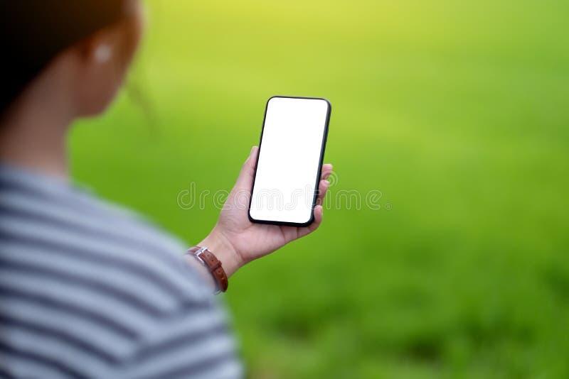 Uma mulher que guarda o telefone celular preto com a tela desktop vazia com fundo verde da natureza do borrão fotos de stock