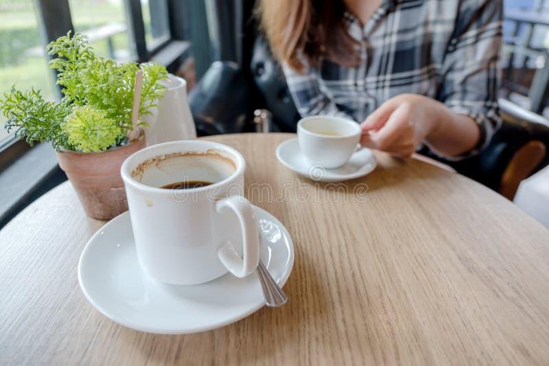 Uma mulher que guarda um copo branco do chá quente com uma caneca de café na tabela de madeira no café fotografia de stock