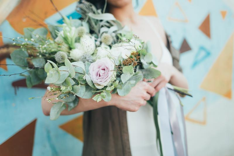 Uma mulher que guarda um grupo de flores coloridas nas mãos estendido imagem de stock royalty free