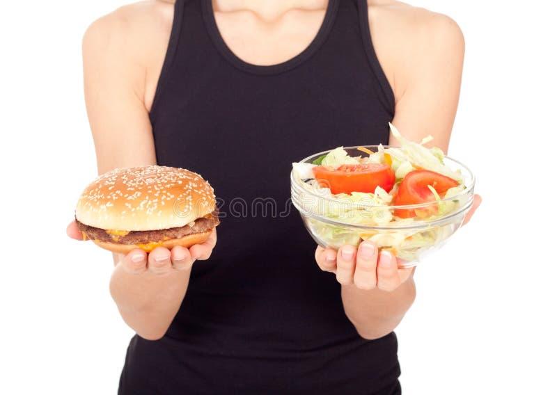 Uma mulher que guarda um hamburguer e uma salada foto de stock royalty free