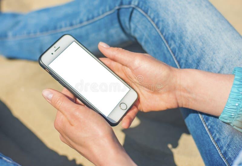 Uma mulher que guarda um telefone celular branco com uma tela vazia imagens de stock royalty free