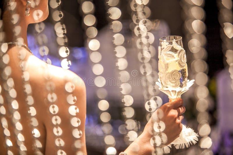 Uma mulher que guarda um vidro do champanhe no copo de água imagem de stock royalty free