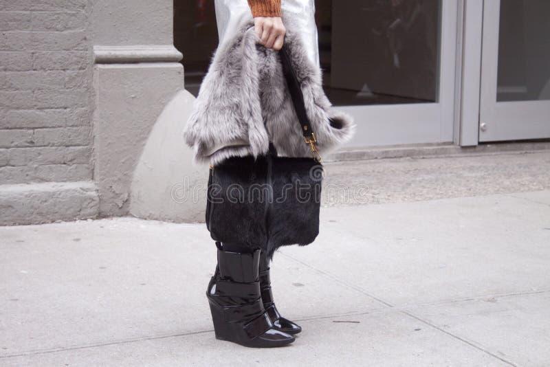 Uma mulher que guarda uma bolsa preta peludo e que veste montantes pretos fotos de stock royalty free