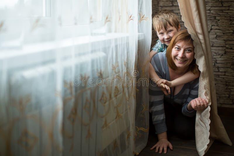 Uma mulher que joga com seu filho novo imagens de stock royalty free