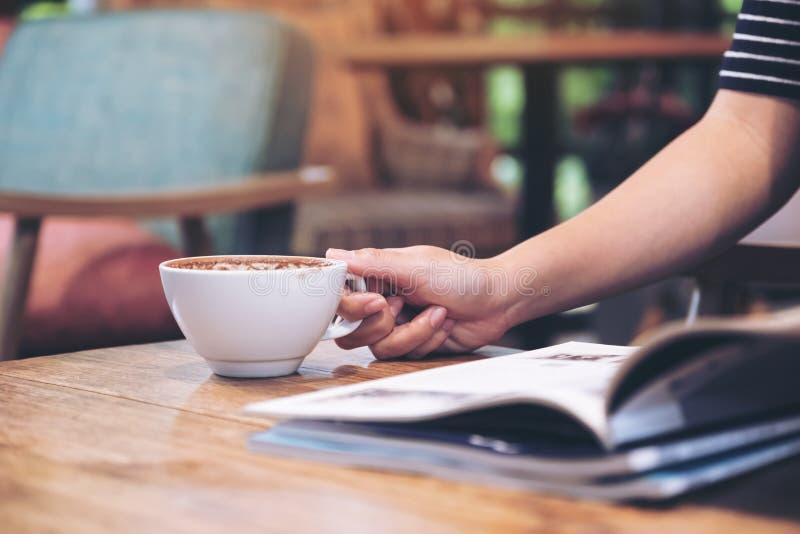 Uma mulher que lê um compartimento com o copo de café na tabela no café fotos de stock royalty free