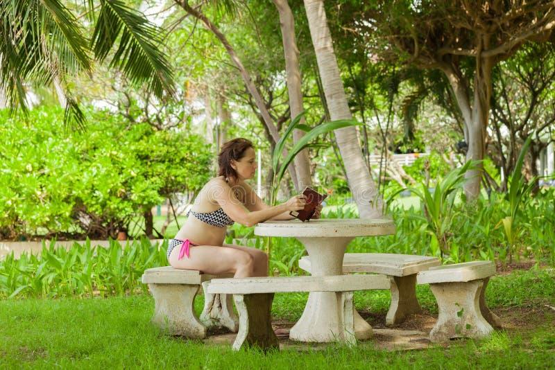 Uma mulher que lê um livro no jardim imagem de stock