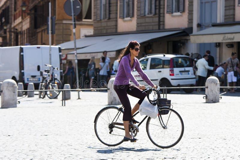 Uma mulher que monta uma bicicleta imagens de stock royalty free