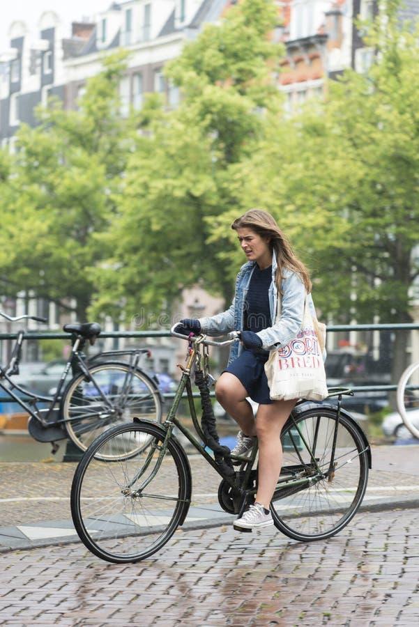 Uma mulher que monta uma bicicleta fotografia de stock royalty free